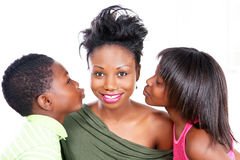 Kissing mom. Smiling mom gets a kiss from loving kids Stock Images