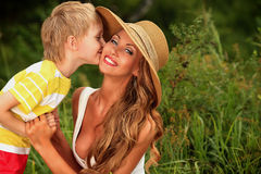 Kissing mom. Happy son kisses his beloved mother. Outdoor Royalty Free Stock Images