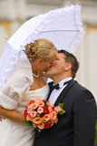 Kissing newlyweds. Portrait of a wedding couple kissing outdoors Royalty Free Stock Image