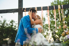 Kissing Newlyweds at Table. Kissing newlyweds at festive table at yard Royalty Free Stock Images