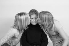 Kissing our brother. Two girls kissing thier younger brothers cheek stock images