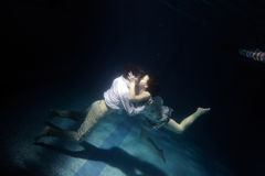 Kissing pair. On bottom of swimming pool Royalty Free Stock Image