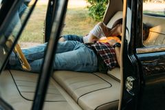 kissing people who are lying in the car and holding hands. look through the window in the car.side view.dressed in a plaid shirt, royalty free stock photography