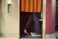 Kissing in photo booth. Young college age couple secretly kissing in retro photo booth Stock Photos