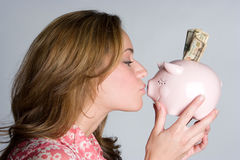 Kissing Piggy Bank. Beautiful woman kissing piggy bank Stock Images