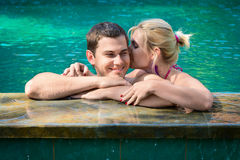 Kissing and relaxing in a swimming pool. Happy smiling young couple relaxing in a swimming pool on a poolside in tropical resort Stock Photo