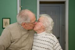 Kissing senior couple. Mature senior couple showing public affection with a kiss Royalty Free Stock Images
