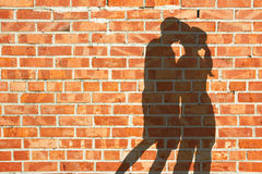 Kissing silhouette couple against red brick wall Stock Photos