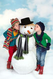 Kissing a snowman. Two little girls in winter dress kissing a snowman Royalty Free Stock Photos