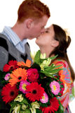 Kissing teenagers with flowers Royalty Free Stock Images
