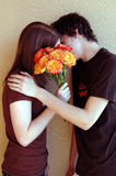 Kissing teens. Two teens kissing secretly against a wall hiding behind roses royalty free stock image