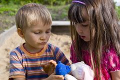 Kissing Toys. Young boy and girl in a sandbox,each holding a stuffed toy.  The are holding the two toys in a kissing position Stock Photos