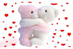 Kissing Valentine bears. Two kissing and cuddling Valentine teddy bears with decorative red love hearts in background Royalty Free Stock Image