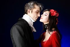 Kissing a vampire. Portrait of a beautiful couple in medieval costumes with vampire style make-up. Shot in a studio Stock Photos