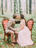 The kissing vintage dressed newlyweds sitting on the old stylish orange chairs in the front of the hanging stump with Stock Photography