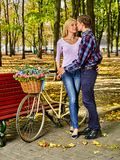 Walking bike of couple in park and kissing walk outdoor. Kissing and walking couple with bike of in park . Summer friends walk outdoor. First date of two young Royalty Free Stock Photos