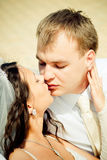 Kissing wedding couple Stock Photos