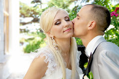 Kissing wedding couple in spring Stock Images