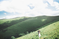 Kissing wedding couple staying over beautiful landscape Royalty Free Stock Images
