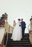 Kissing wedding couple walks upstairs behind old marble figures.  Royalty Free Stock Images