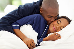 Kissing wife bed Stock Photography