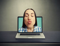 Kissing woman got out of the laptop Stock Images