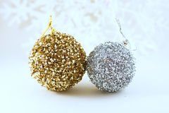 Kissing Xmas balls. Golden and silver Xmas balls on soften snowflakes light background Stock Photos
