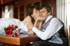 Kissing you. A bride is kissing a groom gently in his cheek, holding his face in her hands Royalty Free Stock Photography