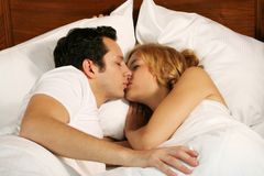 Kissing young couple. A attractive young couple is kissing in their bed at home royalty free stock photos