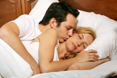 Kissing young couple. A attractive young man is kissing his girlfriend, while the woman is sleeping royalty free stock images