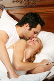 Kissing young couple. A attractive young is kissing in their bed at home royalty free stock images