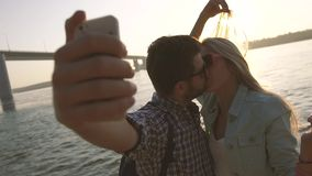 Kissing young couple takes photograph against brightly shining sun and glittering river. Slow motion