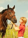 Kissing  of young  girl with your  horse in field Stock Photo