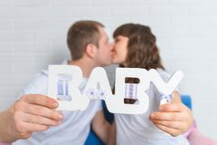 Kissingand enceinte de couples tenant le bébé en bois de lettres, foyer sur le texte Photographie stock