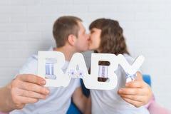 Kissingand grávido dos pares que guarda o bebê de madeira das letras, foco no texto Fotografia de Stock