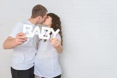 Kissingand grávido dos pares que guarda o bebê de madeira das letras, foco no texto Foto de Stock