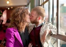 kisssing在里面视窗附近的新夫妇。 免版税库存图片