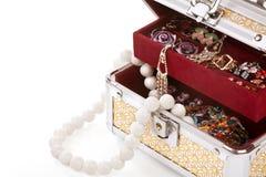 Kist die met kostuumjuwelen wordt gevuld Stock Foto