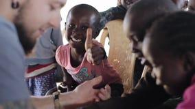 KISUMU, КЕНИЯ - 19-ОЕ МАЯ 2018: Группа в составе маленькие счастливые дети от Африки и кавказец вызываются добровольцем в плохой  акции видеоматериалы