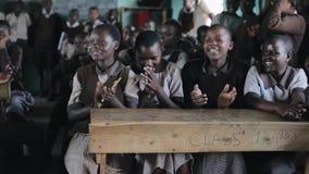 KISUMU, КЕНИЯ - 21-ОЕ МАЯ 2018: Группа в составе счастливые африканские дети сидя в классе и усмехаясь, смеясь над совместно акции видеоматериалы