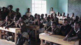 KISUMU, КЕНИЯ - 21-ОЕ МАЯ 2018: Толпа облыселых африканских детей сидя на столах школы Мальчики и девушки, подростки внутри сток-видео