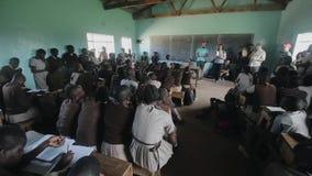 KISUMU, KENIA - 21 DE MAYO DE 2018: Grupo de voluntarios caucásicos en la pequeña escuela en África Los niños escuchan en una sal metrajes