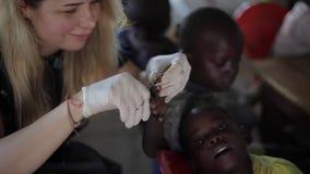Kisumu, Kenia - 24 de mayo de 2018: Niños de ayuda de la mujer caucásica de África Hembra que corta sus clavos con las tijeras almacen de video