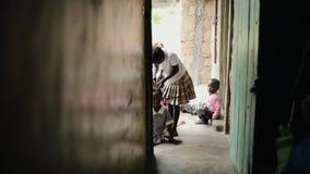 KISUMU, KENIA - 15. MAI 2018: Afrikanische Kinder sitzen nahe dem Haus Kämme eines kleinen Mädchens, flicht ihr Schwester ` s Haa stock footage