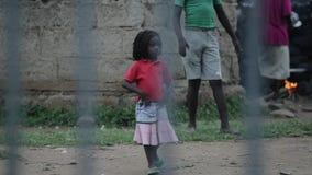 KISUMU, KENIA - 23. MAI 2018: Ansicht durch den Zaun Gruppe afrikanische Leute, die draußen Zeit verbringen Kleines Mädchen, das  stock video