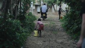 Kisumu, Kenia - 17. Mai 2018: Hintere Ansicht des afrikanischen Mädchens den Kanister mit Wasser tragend Kind, das durch Straße g stock footage