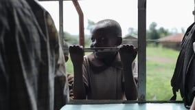 KISUMU, KENIA - 21. MAI 2018: Porträt des kleinen afrikanischen Jungen, der, Gitter an halten lächelt Nette männliche Ausgabenzei stock footage