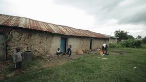KISUMU, KENIA - MEI 15, 2018: De Afrikaanse familie, de kinderen en de moeder bevinden zich dichtbij hun huis in slecht dorp in A stock video
