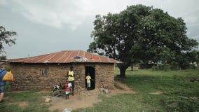 KISUMU, KENIA - MEI 15, 2018: De slechte Afrikaanse familie bevindt zich dichtbij hun huis Mamma en kinderen in een dorp in Afrik stock footage