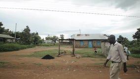 KISUMU KENJA, MAJ, - 15, 2018: Biedna Afrykańska wioska Ludzie angażują w ich dziennych sprawach dziecko niosą klingeryt zbiory
